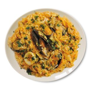 Risotto di Mare, Rice, fish concentrate, clams sauce, squid rings, mussels, peeled shrimps, clams on plate ready meal Italian