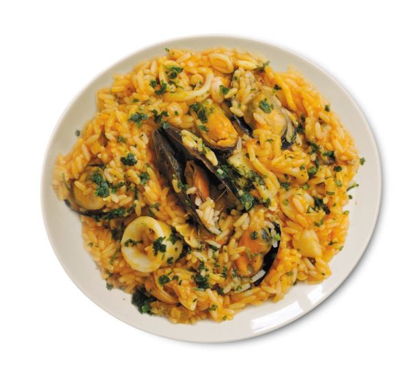 Risotto di Mare, Rice, fish concentrate, clams sauce, squid rings,mussels, peeled shrimps, clams on plate ready meal Italian